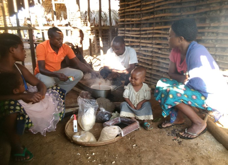 A demonstration on how to make an enriched porridge by a community health volunteer. All the ingredients are neatly displayed in the basket in the foreground.