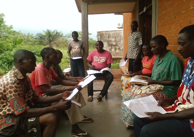A CEUM community animator meets with community health volunteers to discuss the screening data and household visit data they have collected.