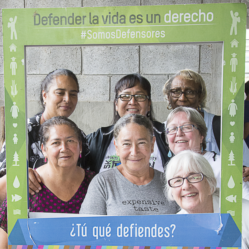 "Women ""defenders of human rights and of nature"" pose with women from PC(USA) Peacemaking, Climate Justice and Faith delegation. Photo frame reads: Defending life is a Right. #WeAreDefenders. What do YOU defend?"