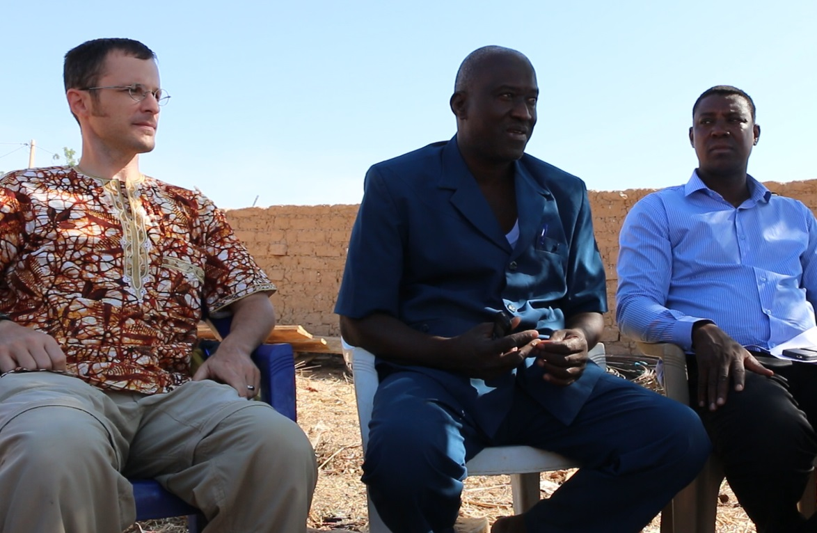 Michael (left) and church leaders listening to the village mayor (center) tell the story of a top student without a place to live.