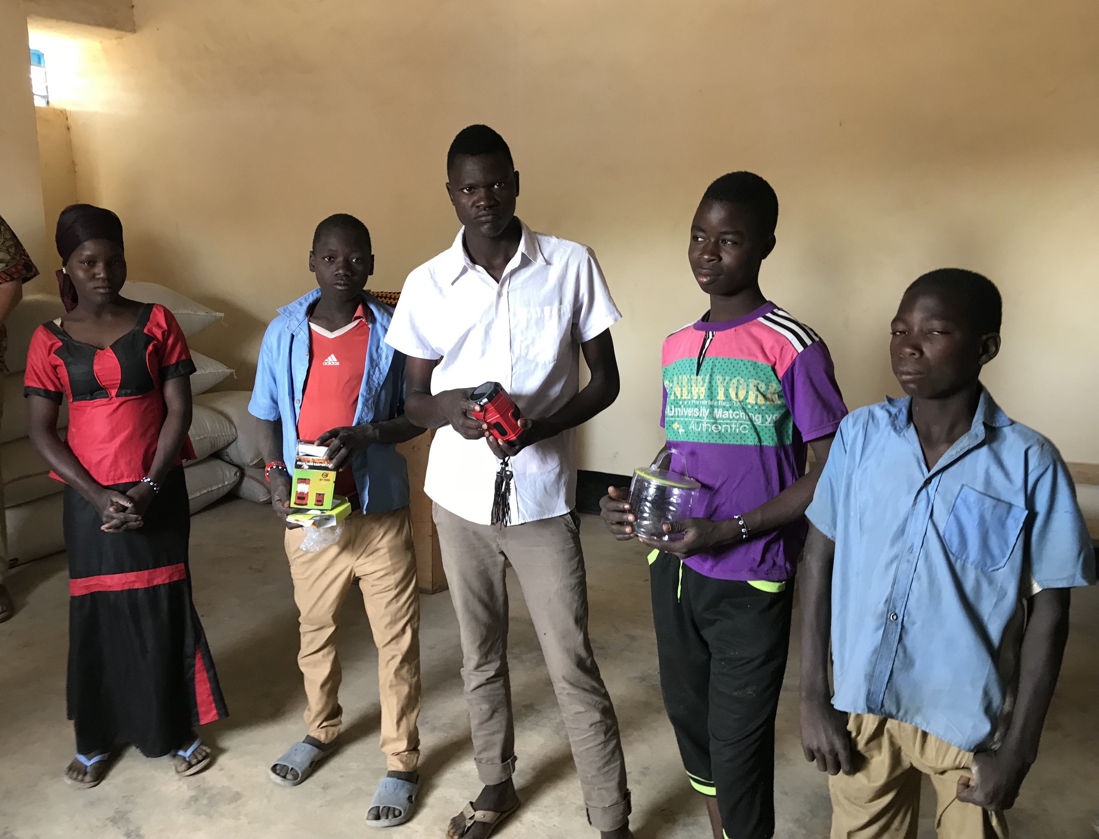 Students at the second hosting center receiving solar lights to help them study at night.