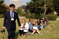 A photographer sets up a photo to include Young Adult Volunteers and students of several nationalities to promote a Korean language contest. Photo credit: Alyson Kung