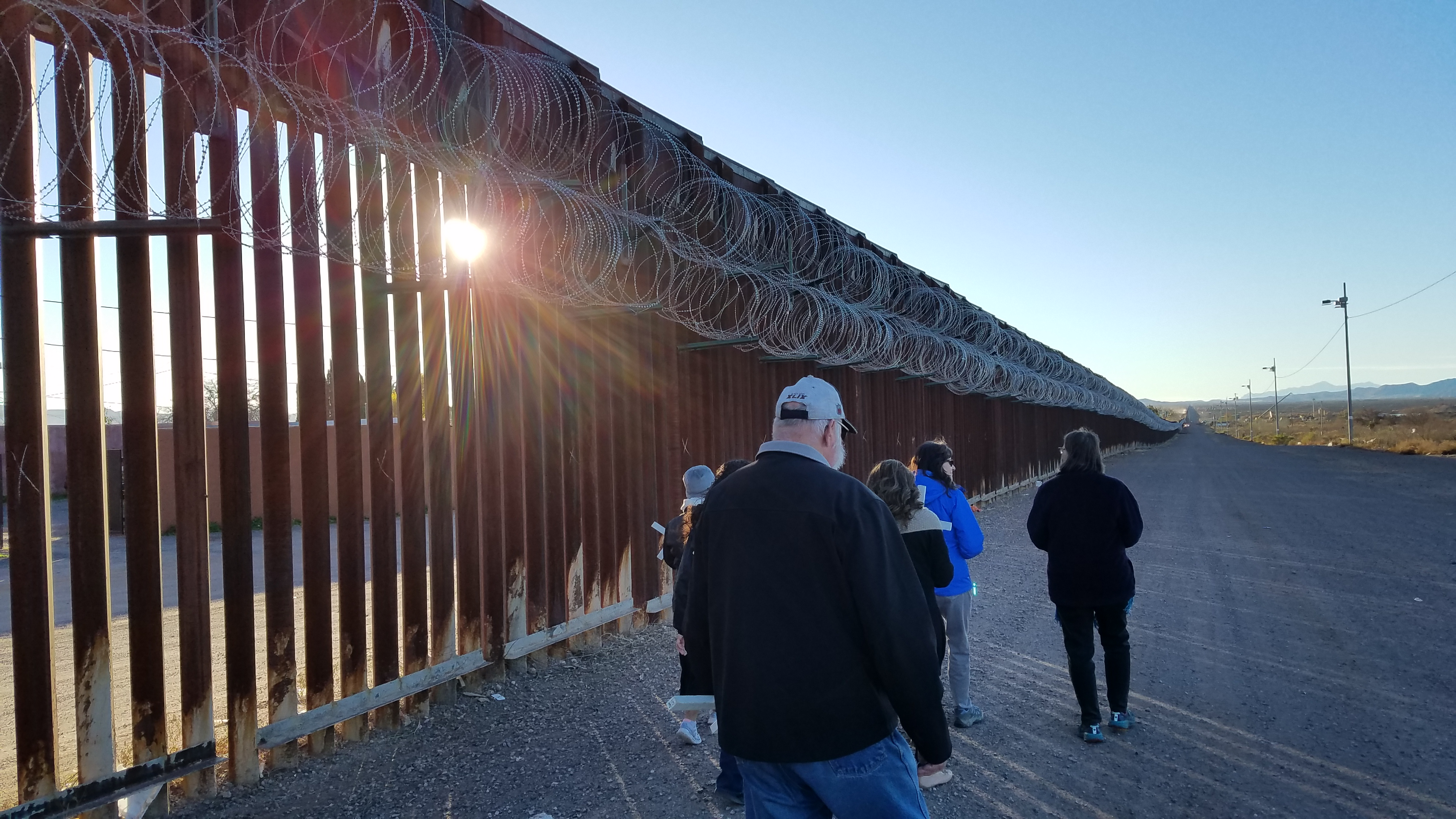Participants in the Posada Sin Fronteras walking in the shadows of the steel dividing wall with newly installed concertina/razor wire on the United States/Mexico border.