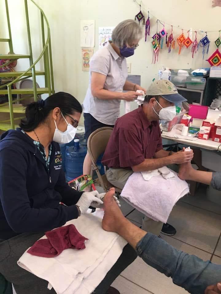 Sister Maribel Lara and Dr. Marino caring for the feet of guests at the MRC. (Photo credit Sister Judy Bourg)