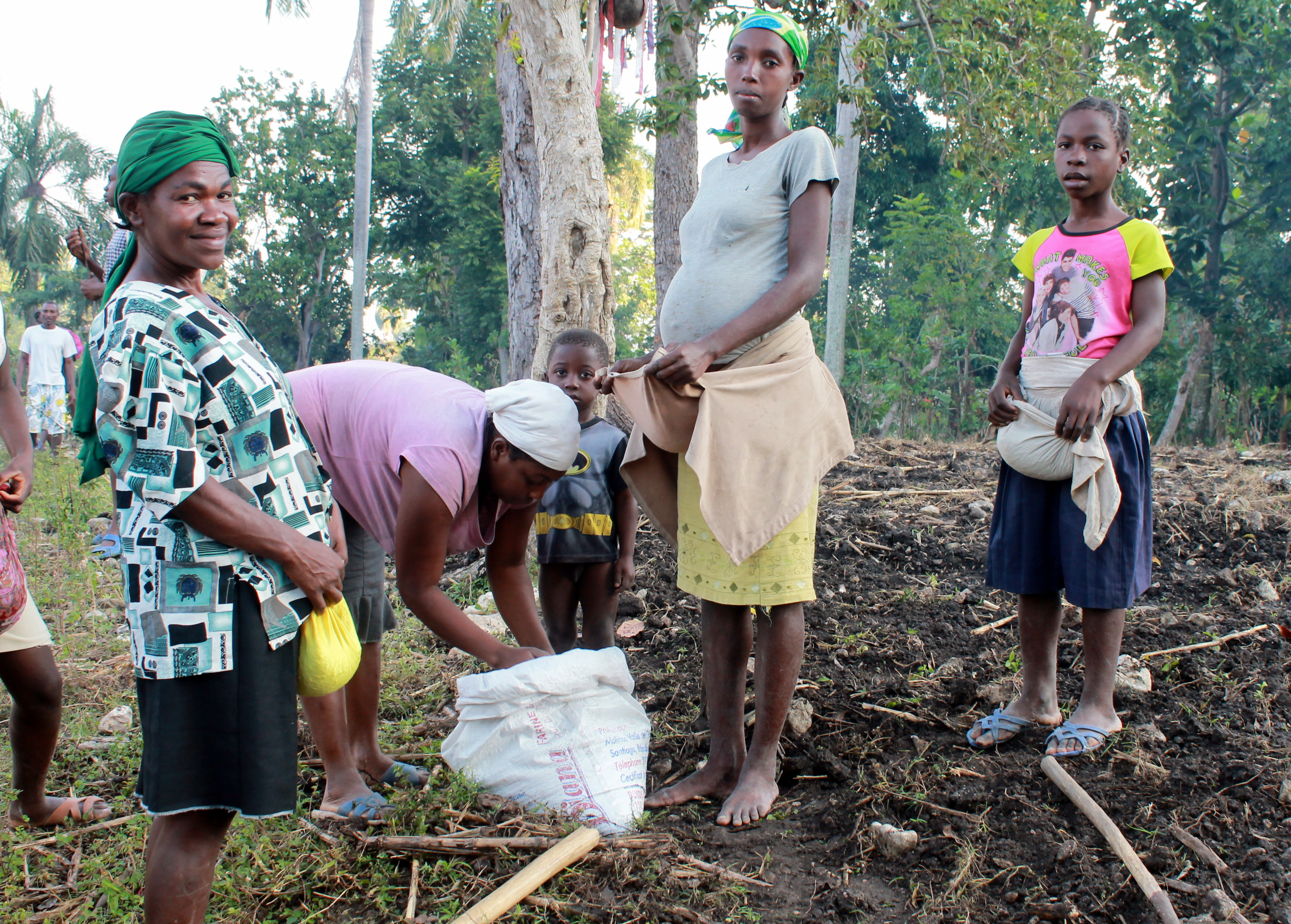 """Women in Dofine, Verettes, preparing for a day of planting beans in a field irrigated by the local river, 2000 feet above sea level. They are part of a """"konbit"""" which is a Haitian Creole word for something like a barn-raising -- neighbors coming together to help each other with their field work."""