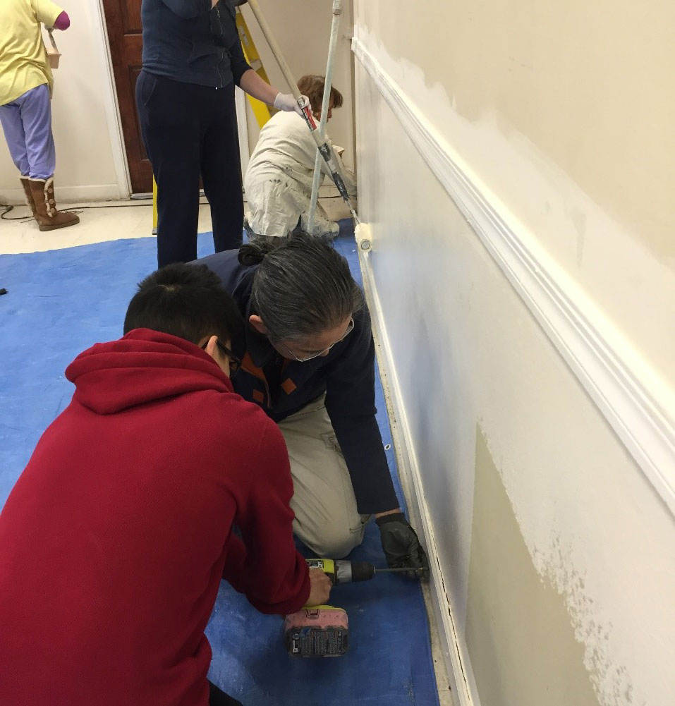 Dr. Richard Chan and Jonathan Chan of the Tenafly church work to fix a wall at the Mideast Evangelical Church.