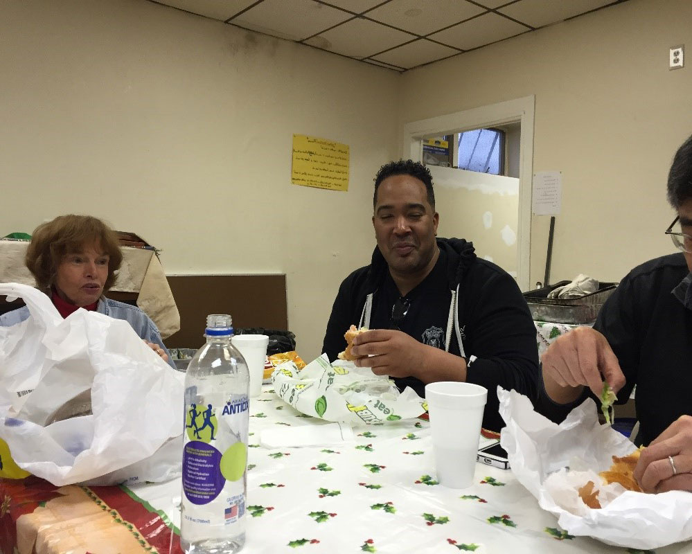 Carole Bayley (left) of the Tenafly church enjoying food with other volunteers.