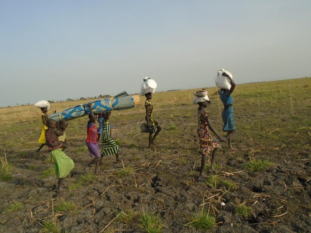Sudanese women travel back to their village with supplies. (Photo credit: Hope Restoration South Sudan)