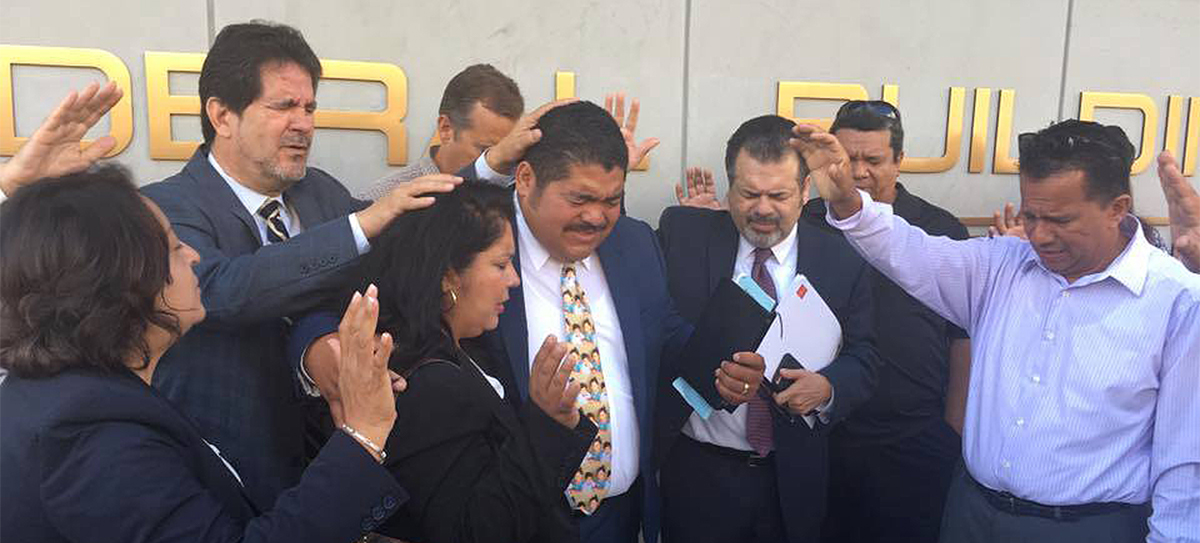 Pastor Noe Carias was surrounded by prayers just before he was taken away in handcuffs.