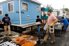 Guillermo López-Acosta(left), the Rev. Sam Weddington (second from right) and volunteers work to hoist a trailer in the Metropolitan Mobile Home Park in Moonachie, New Jersey.