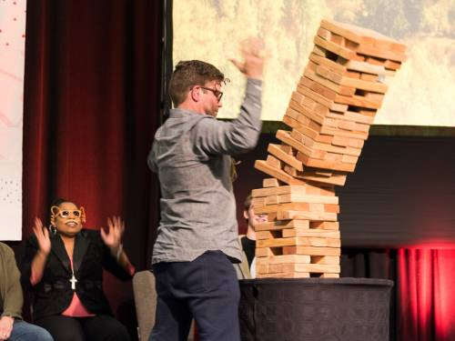 Denise Anderson, co-moderator of the 222nd General Assembly of the PC(USA), reacts as Carl Horton lifts his hands when the Jenga tower on stage at the APCE 'Holy Humor' worship service collapses. (Photo by Gregg Brekke)
