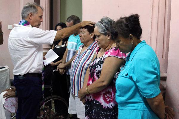 The Rev. Ary Fernandez baptizes Xiomara Alonso as other new members of the Presbyterian Mission in Holguín look on. (Photo by Raiza Ortega)
