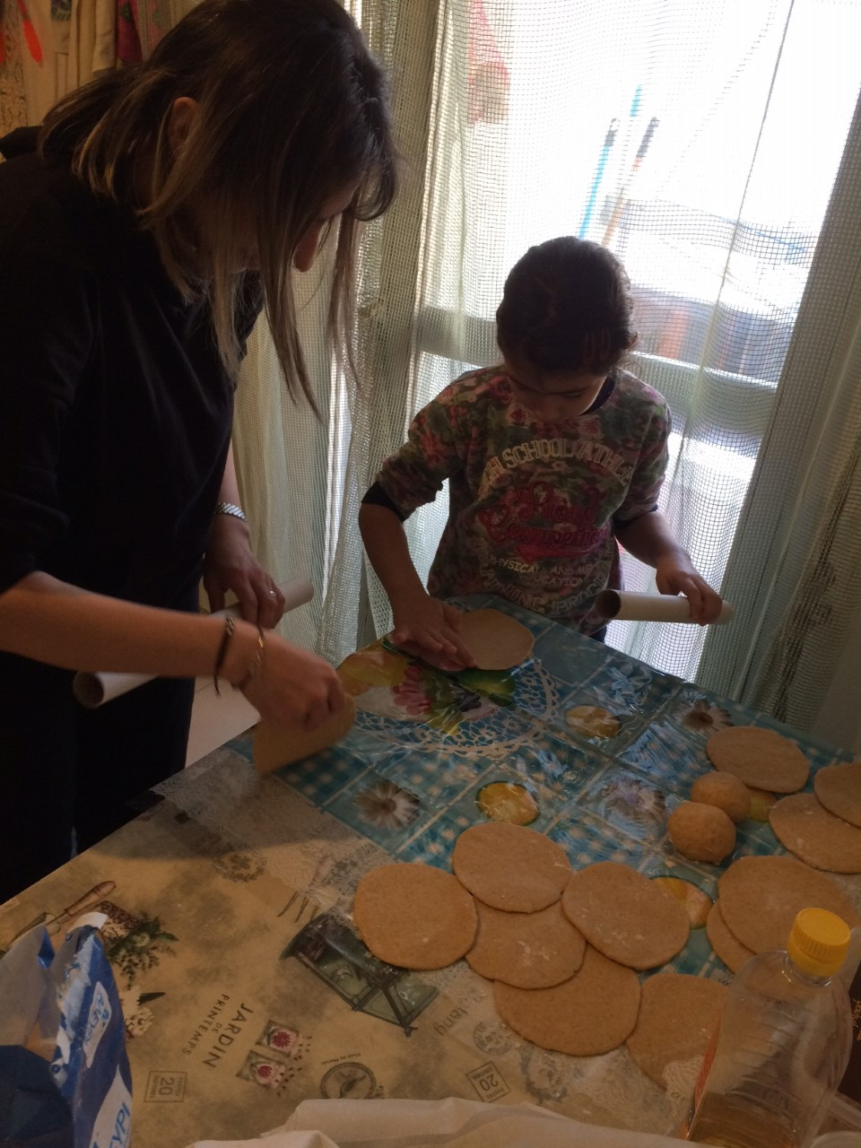 Mother and daughter help me make Pita bread.