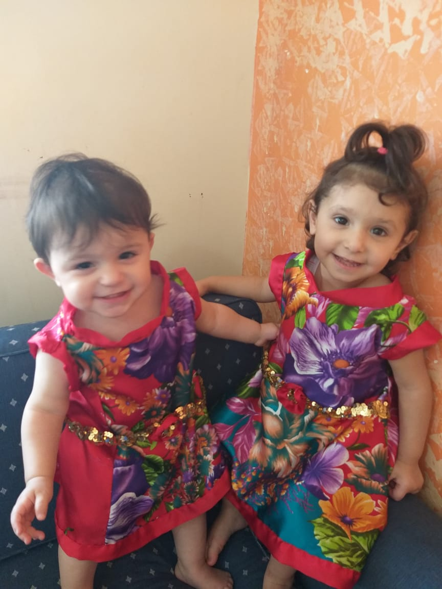 One dress makes two dresses for two little girls.