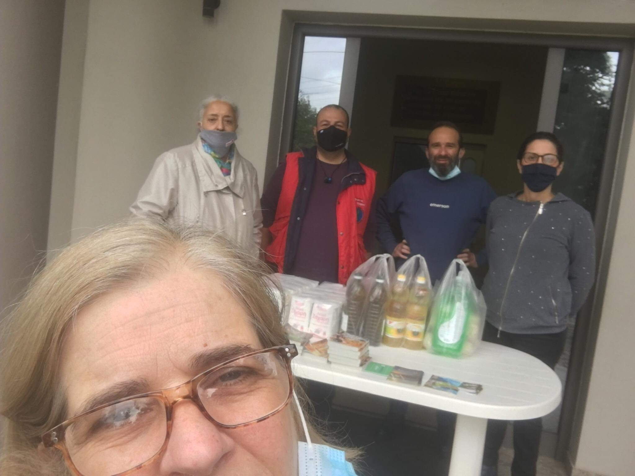 The compassionate staff at Perichoresis gathers to organizes food deliveries.