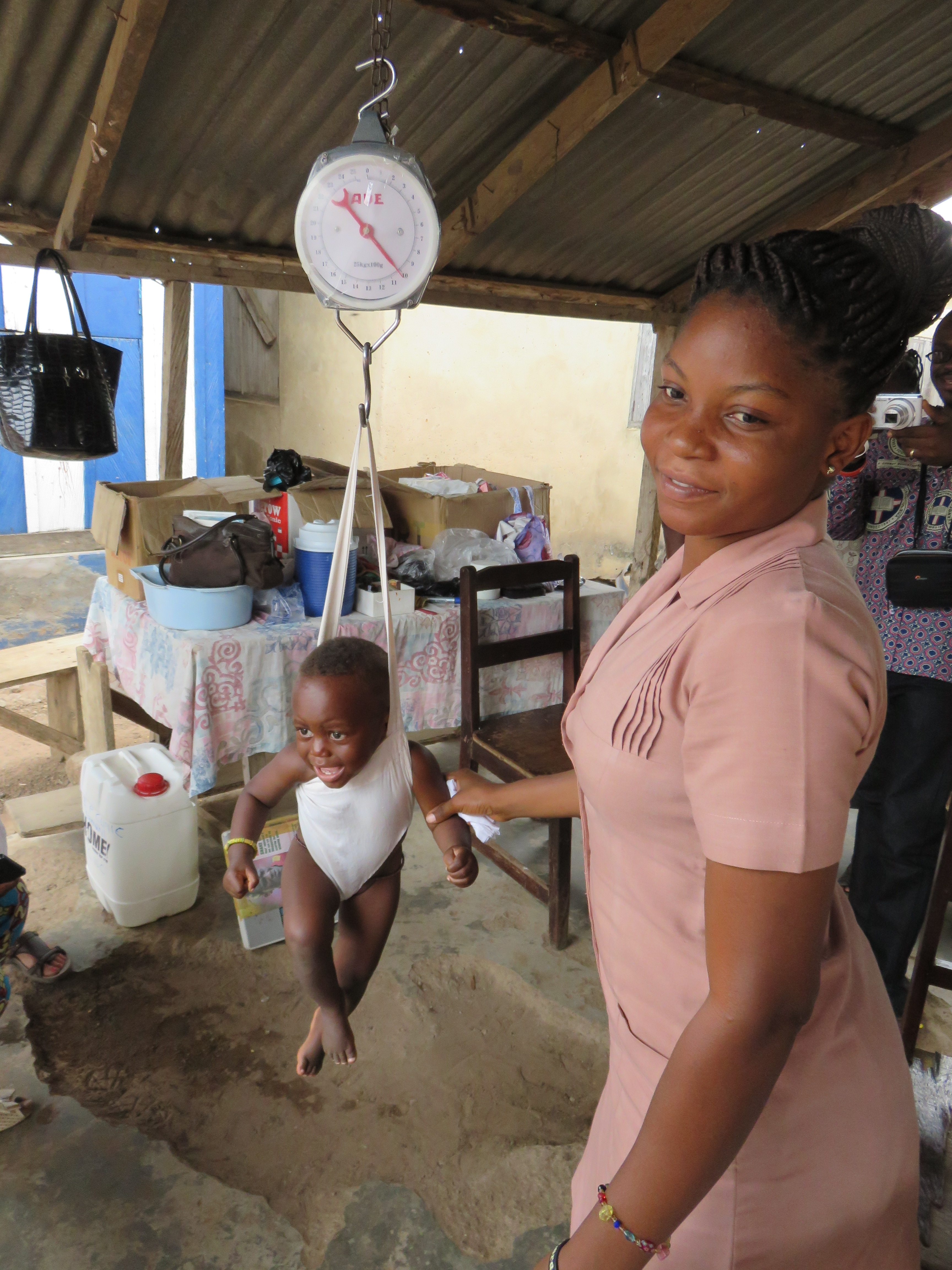 A midwife at the Dzemeni maternity clinic in Ghana, supported by First Presbyterian Church of Fairfield, Connecticut, weighs an infant to check on healthy growth and development. (Photo by Josh Heikkila)