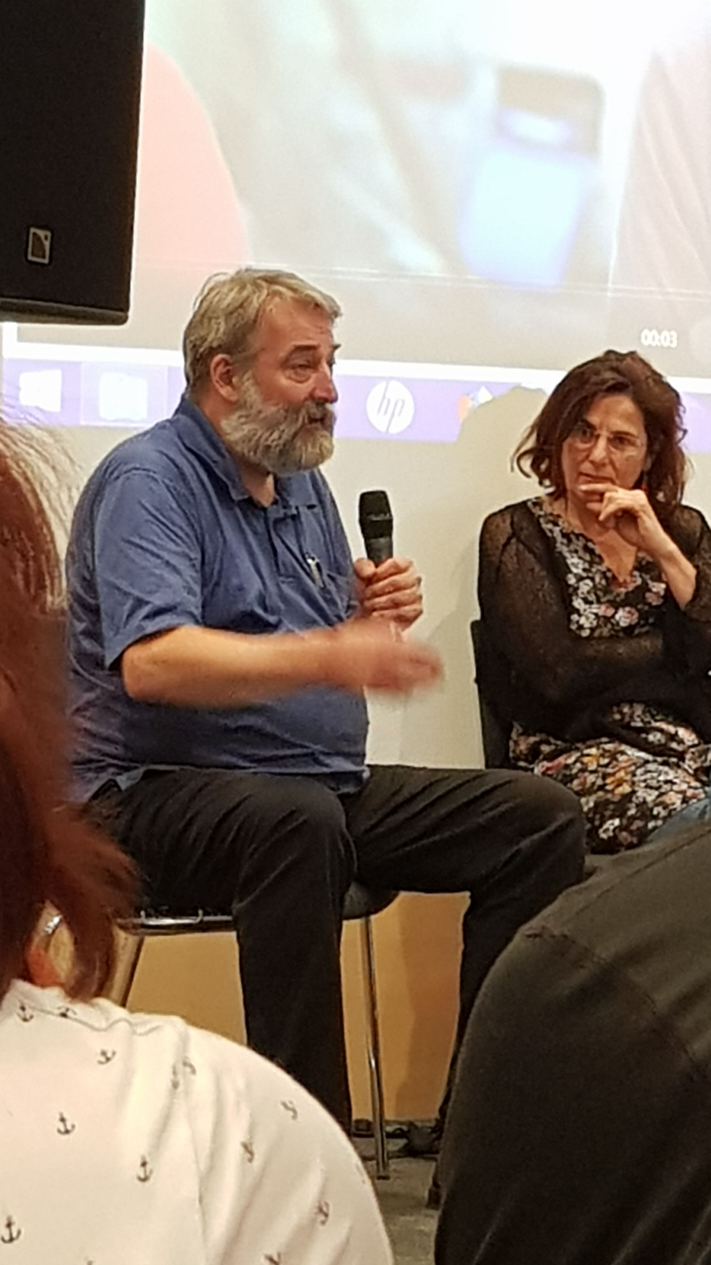 """Efi Latsoudi of Lesvos Solidarity and Otfried Nassauer of Information Center for Transatlantic Security at a Kirchentag panel. """"Open borders for refugees but close boarders for arms export."""""""