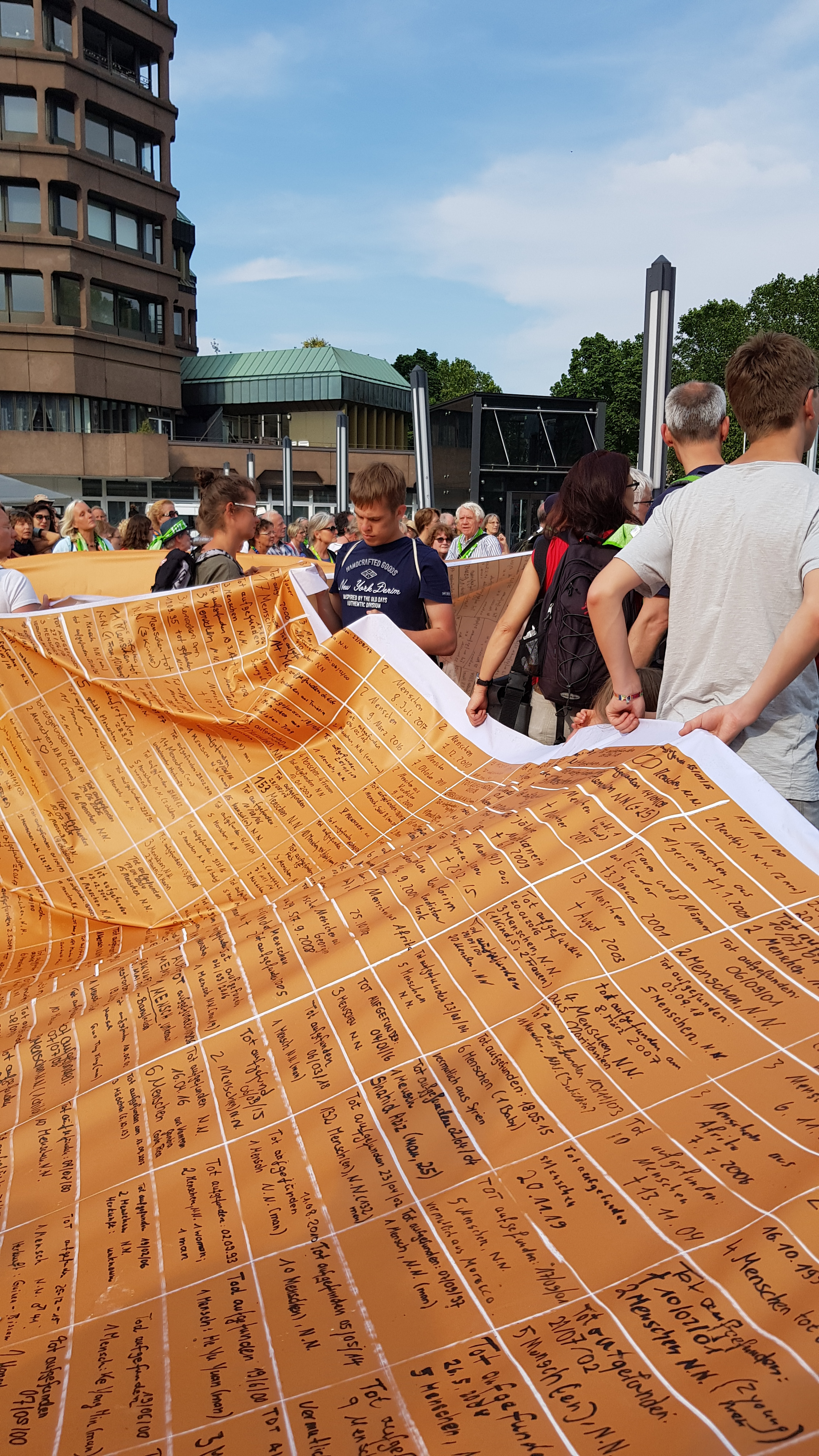 We are carrying a large banner with names of drowned refugees through the city of Dortmund during a silent demonstration at the German Kirchentag.
