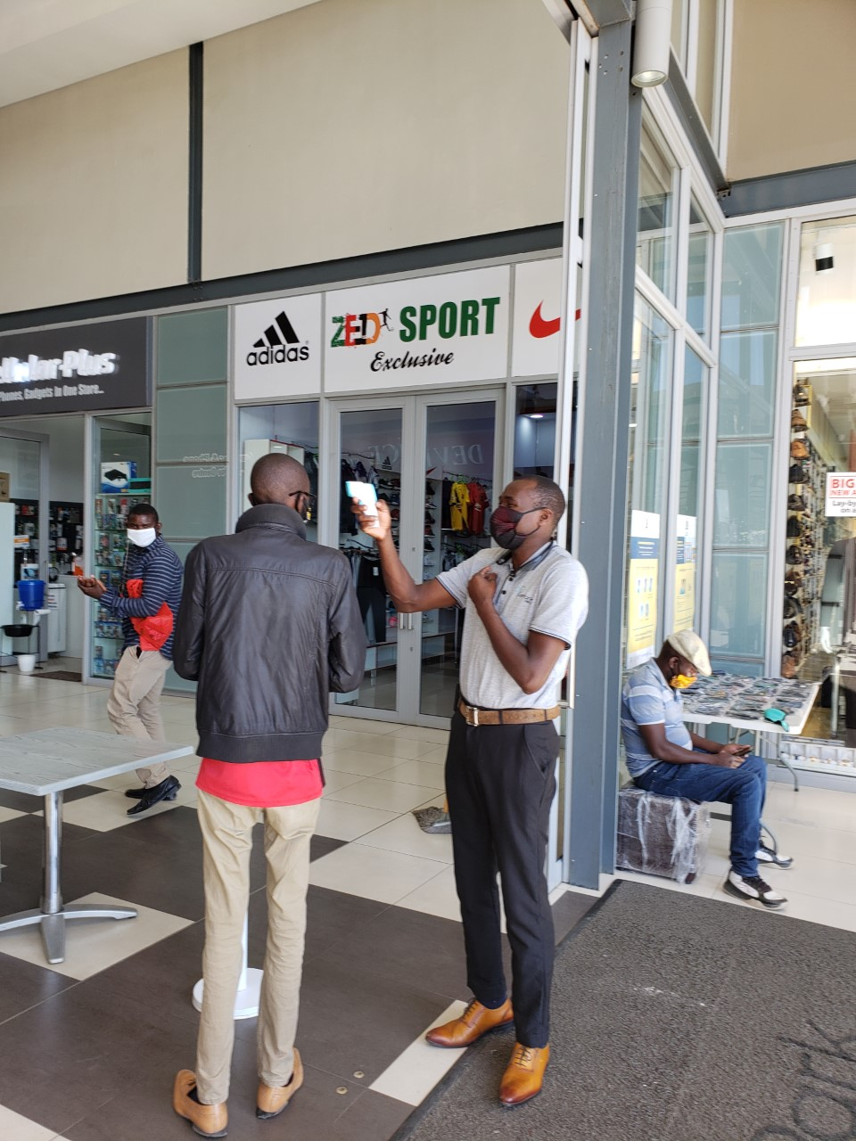 The temperature tester and a patron at the entrance of East Park Mall. (Photo by Rev. Paula Cooper)