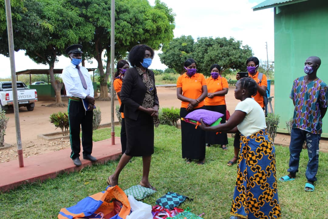 Church of Central Africa Presbyterian (CCAP) Health Department and Days for Girls (in orange t-shirts, Mrs. Stella Mwanza, Mrs. Mirian Nyirenda, Mrs. Cecilia Shawa, Mrs. Eunice Zimba) at a prison distributing the Days for Girls Supreme Sanitary Kits for the female prisoners. The woman in the brown suit is Mrs. Margaret Msimuko, Lundazi (Zambia) district council chairperson. The other woman receives the Supreme Sanitary Kits made by the Days for Girls department. Photo by Cynthia Mtalanga.