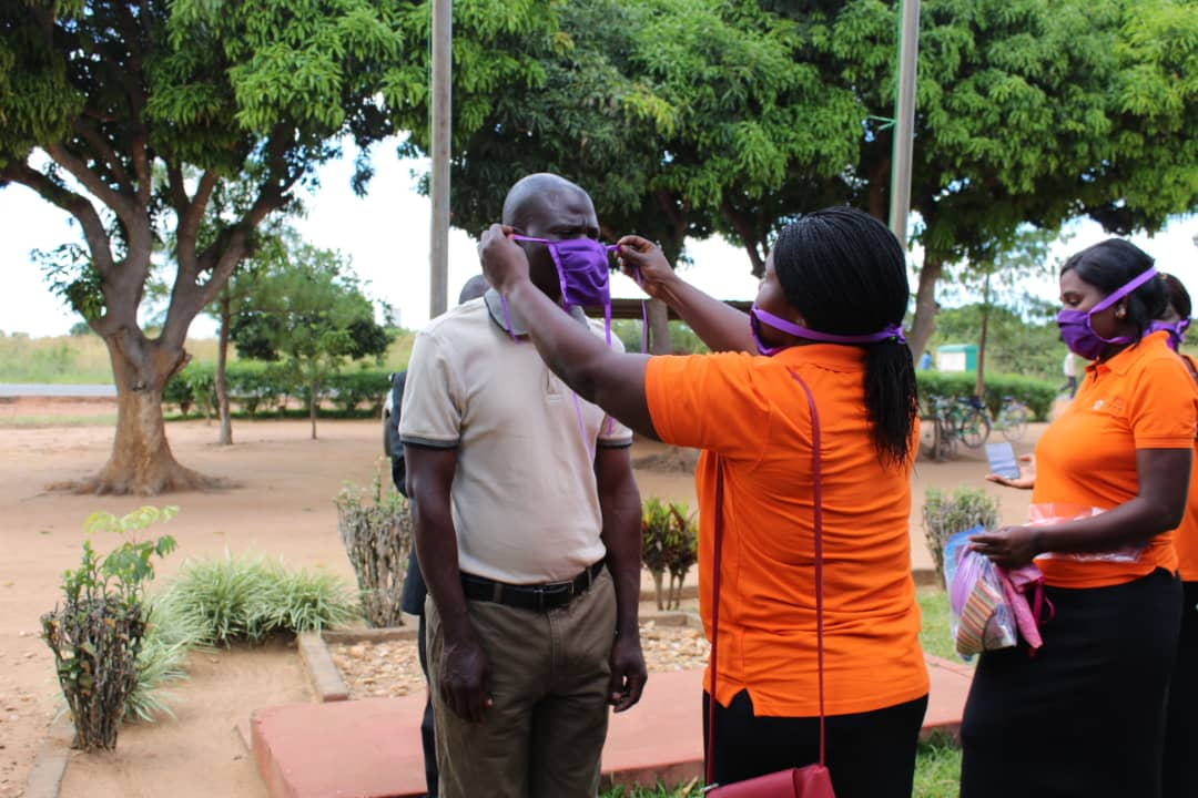 A woman from Days for Girls department demonstrates how the mask is placed.  (Photo by Cynthia Mtalanga)