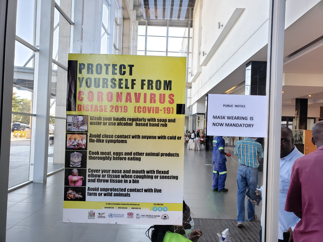 The entrance at Levy Mall. The person sitting in the fluorescent yellow shirt (foreground) sprays patrons' hands with sanitizer. (Photo by Rev. Paula Cooper)