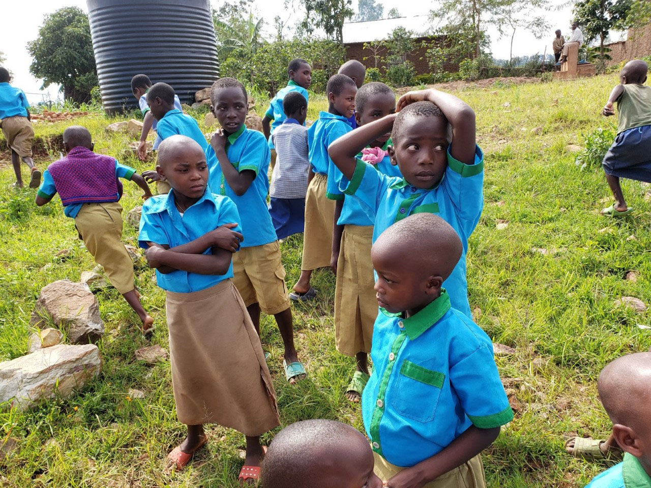 Children at Kinihira Sub-parish during recess. At the top left-hand corner the water tank that collects the rainwater. At the top right-hand corner, the unworkable water system.