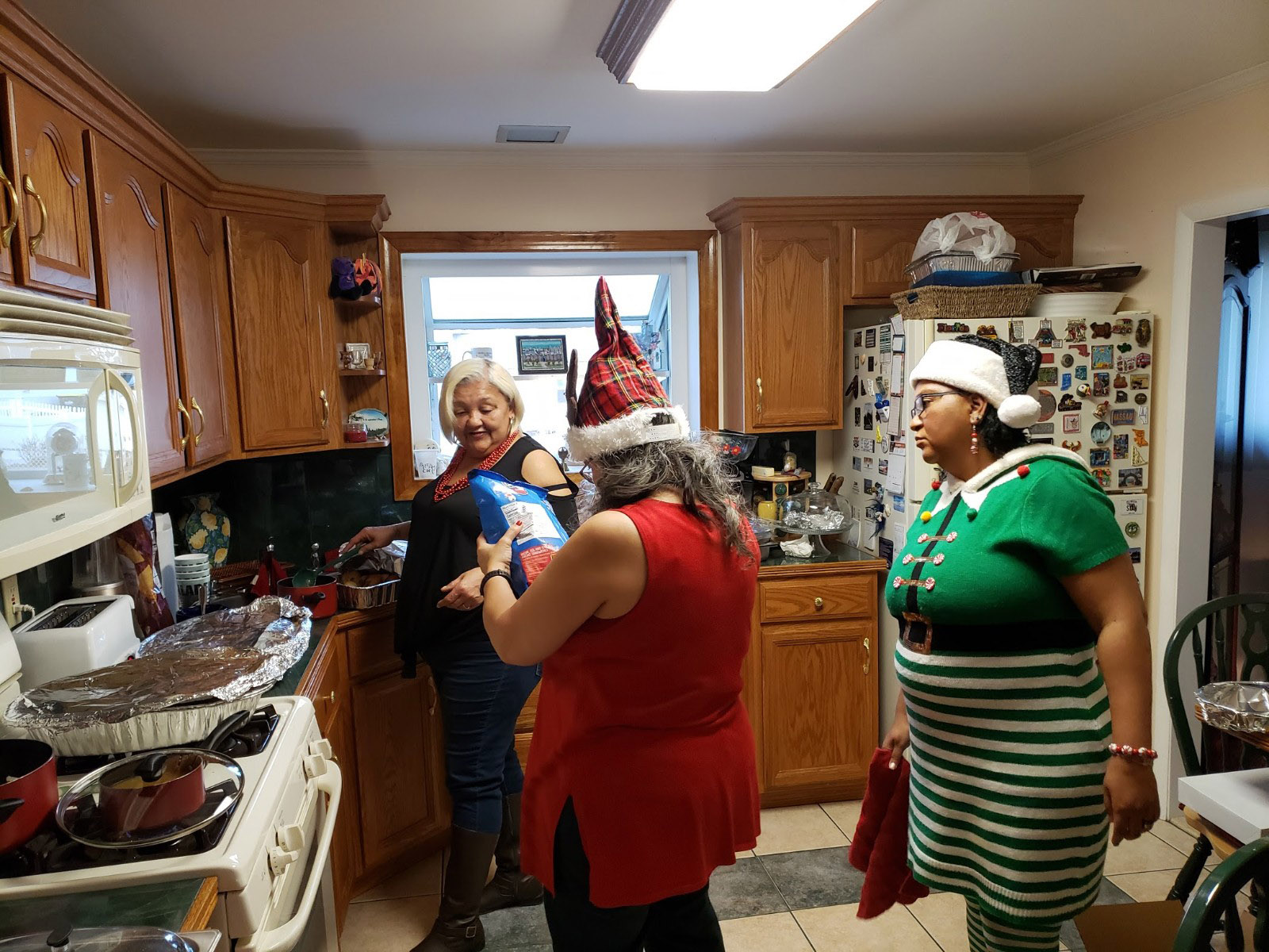 My sisters Renee and Terri Lynn and cousin, Anissa, preparing Christmas dinner. Photo by Paula Cooper.