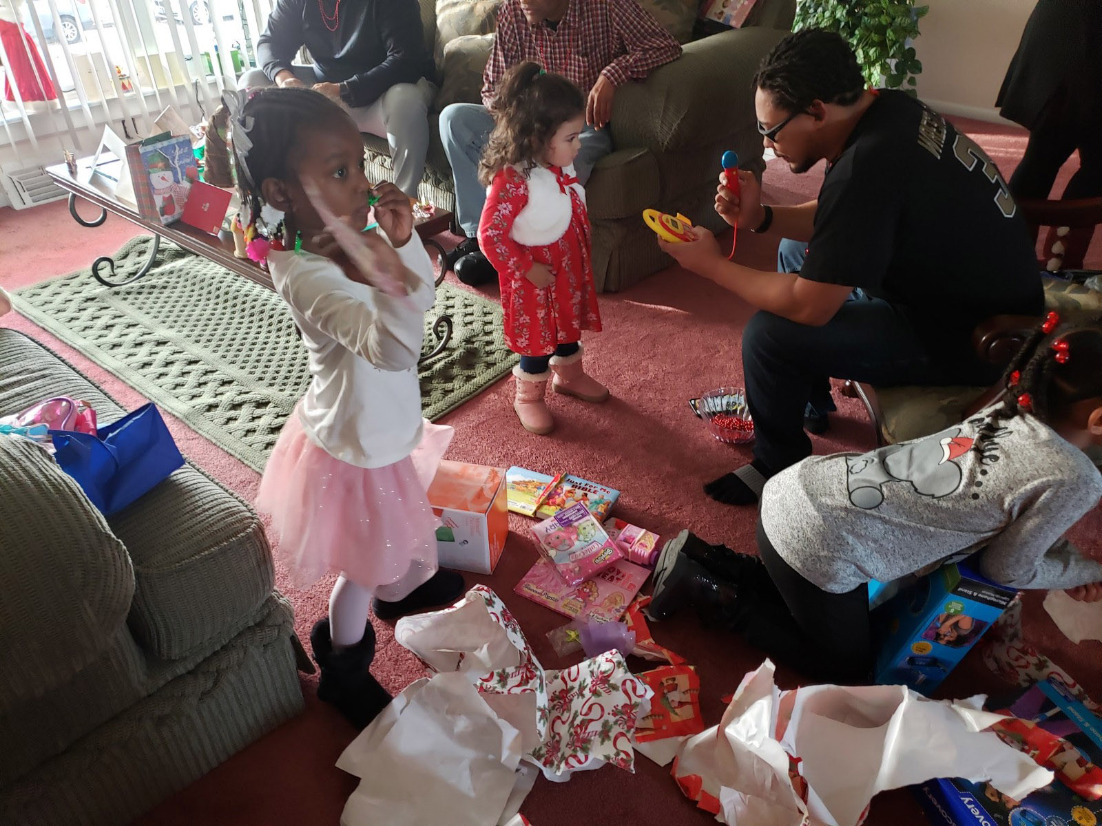 My great nieces opening Christmas present at Renee's home and nephew, Dion, assisting his niece (one of my great nieces). Photo by Paula Cooper.