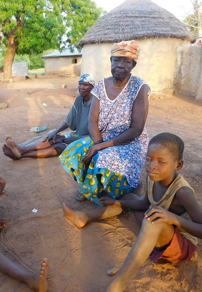 After living 26 years alone in the Gnani Camp, Mrs. Wapu (center) was taken home to live with her son.