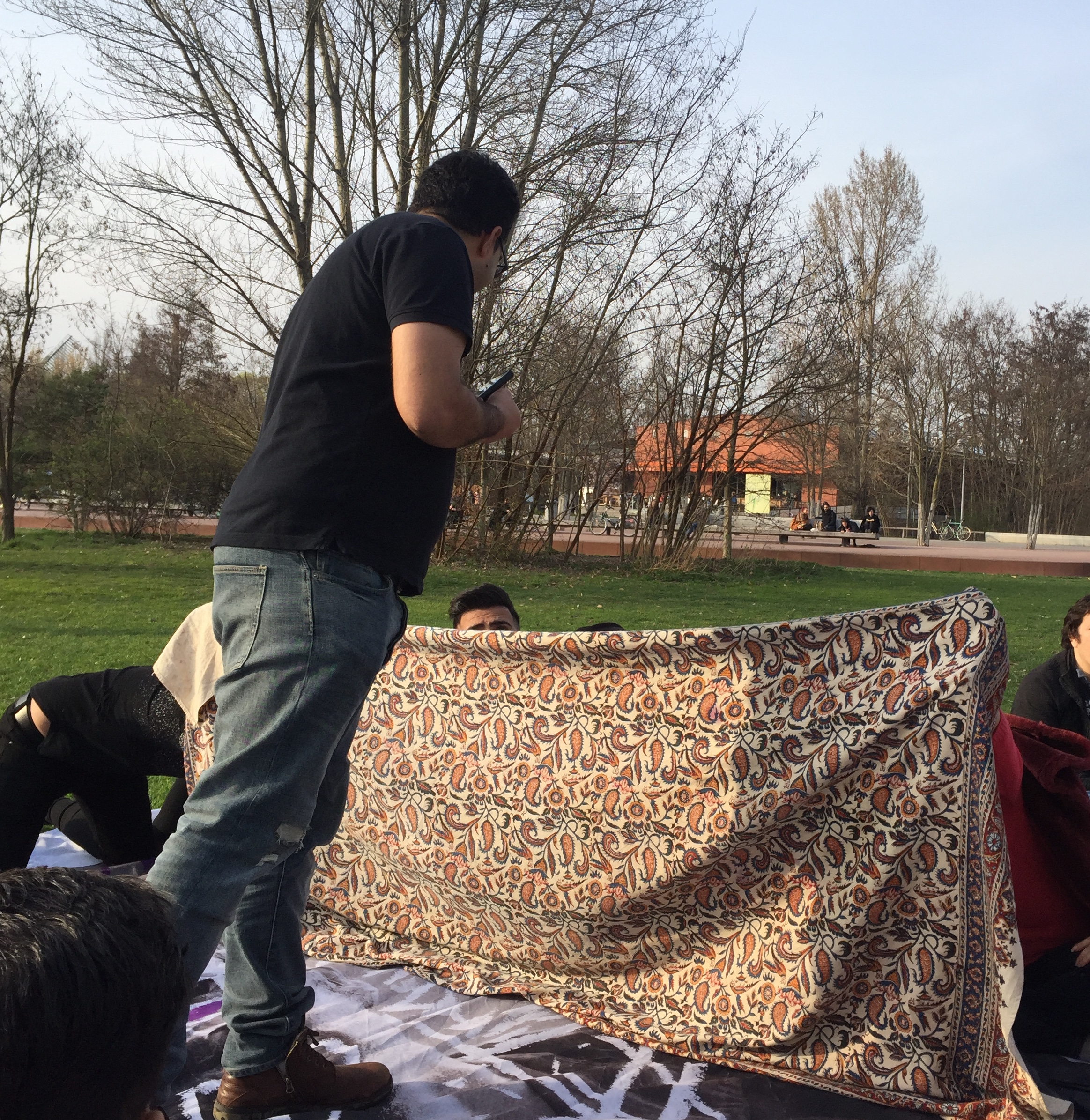 Playing traditional guessing game during park gathering. One team hides behind the blanket while they pass a ring to someone's hand. The other team then has to guess who has it.