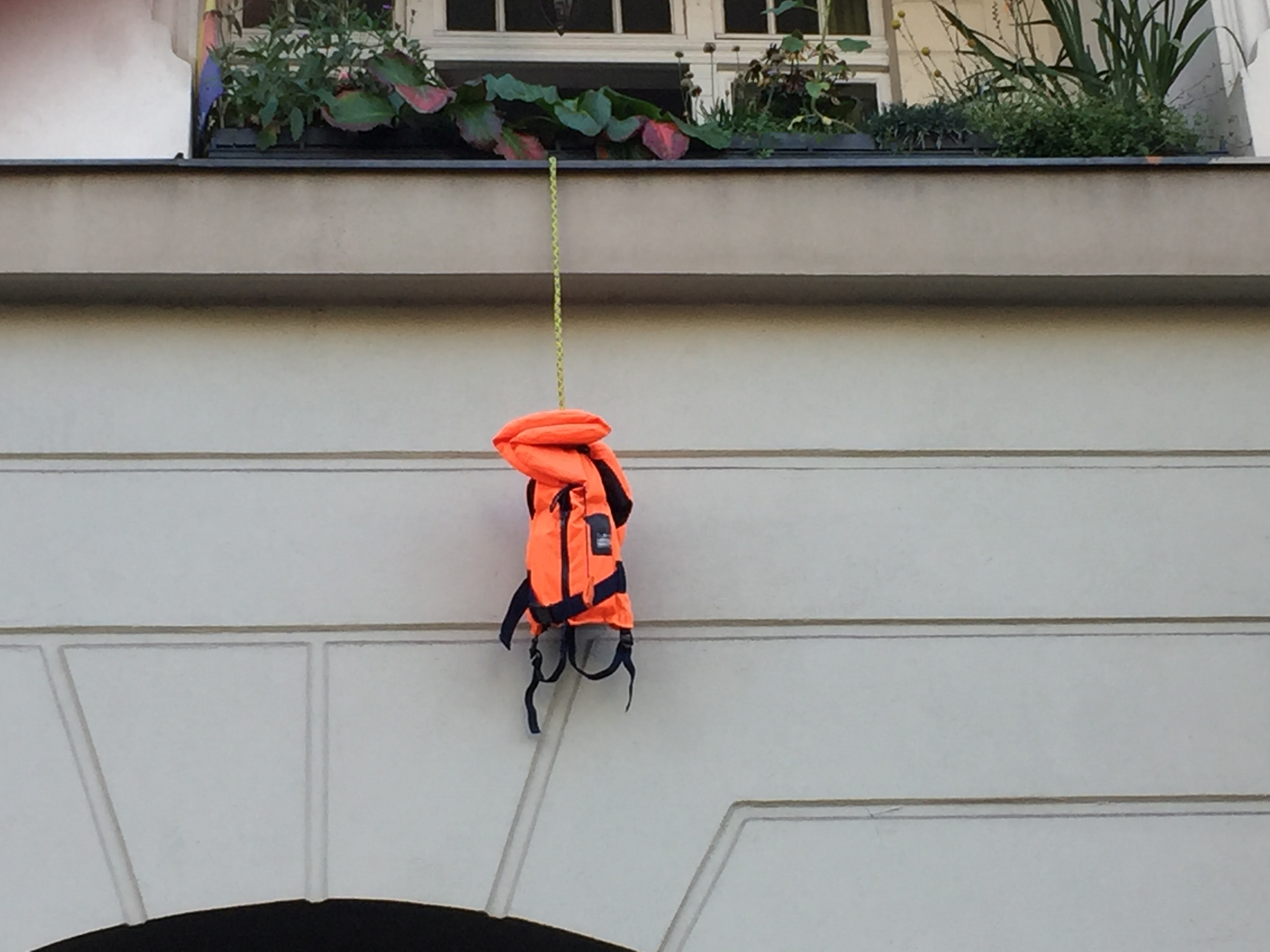 A life vest hangs lifelessly from a balcony in Berlin-Kreuzberg, a stark reminder of all the many people who have been forced to use such vests in sea crossing attempts, who either reached their destination or died or were turned back in trying.