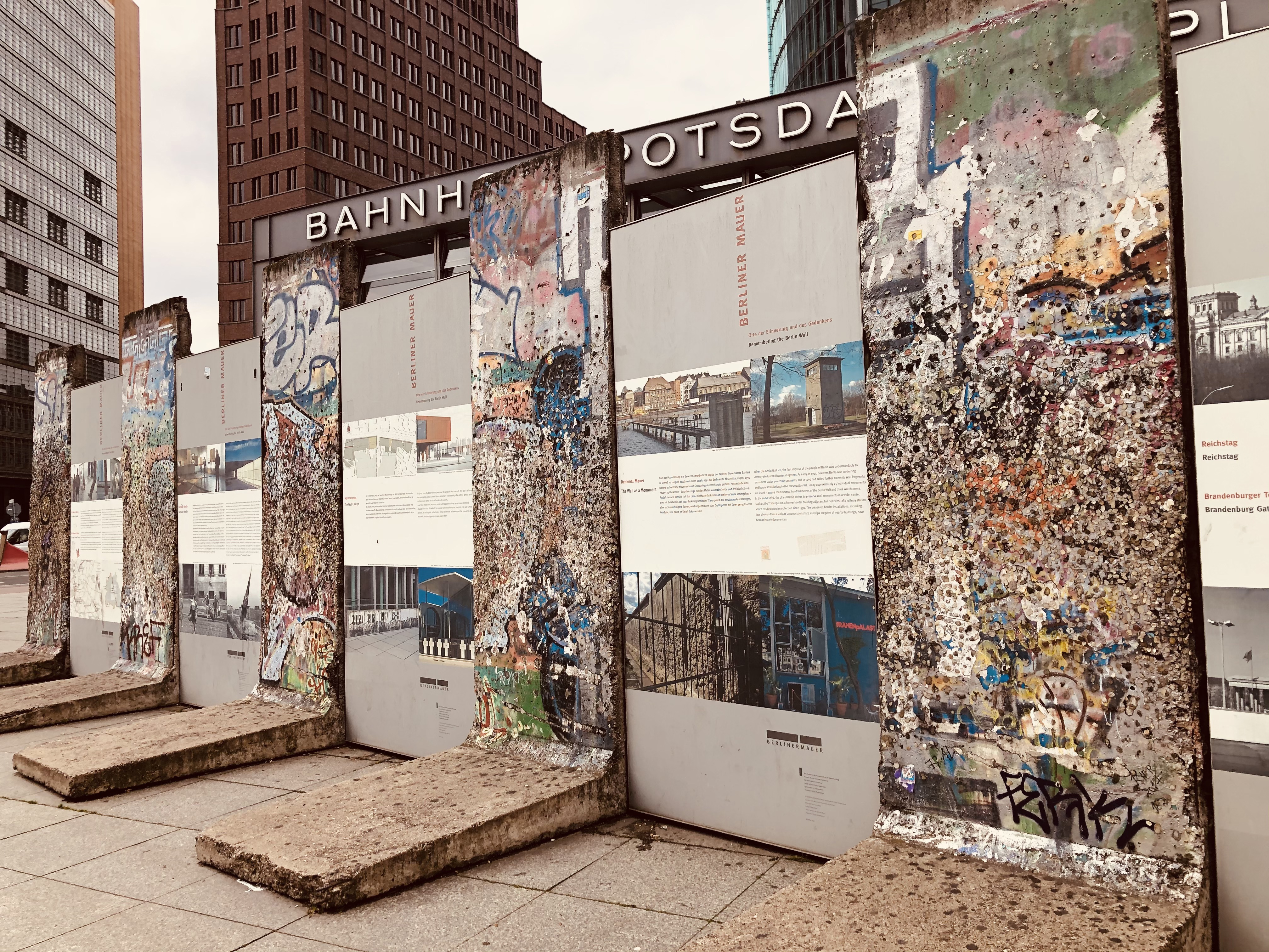 Sections of the wall stand at Potsdamer Platz, Berlin, along with photos and a memorial to those who fought against the divisions created by the wall.