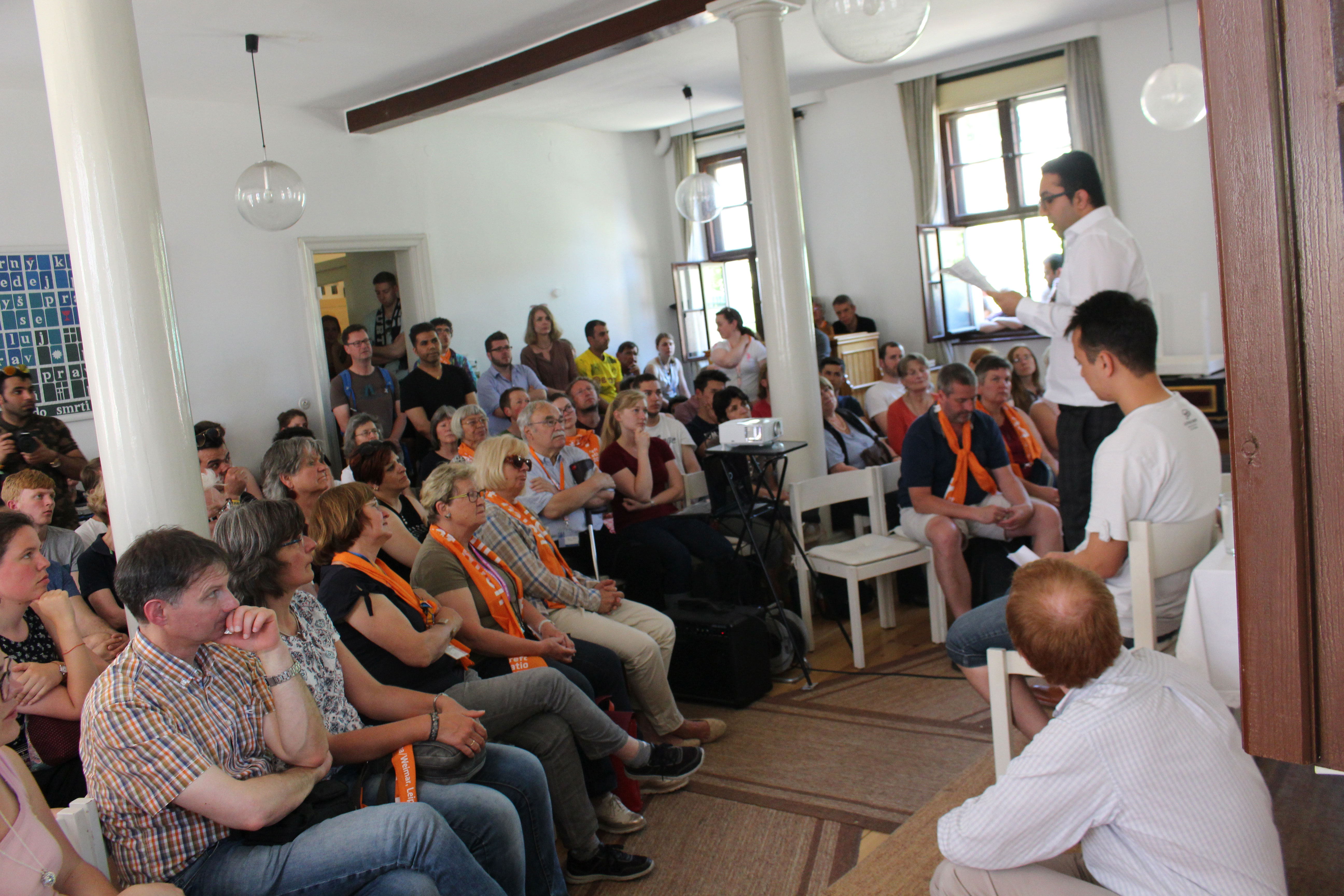 Ryan (seated) looks on as stories are shared with the Kirchentag group
