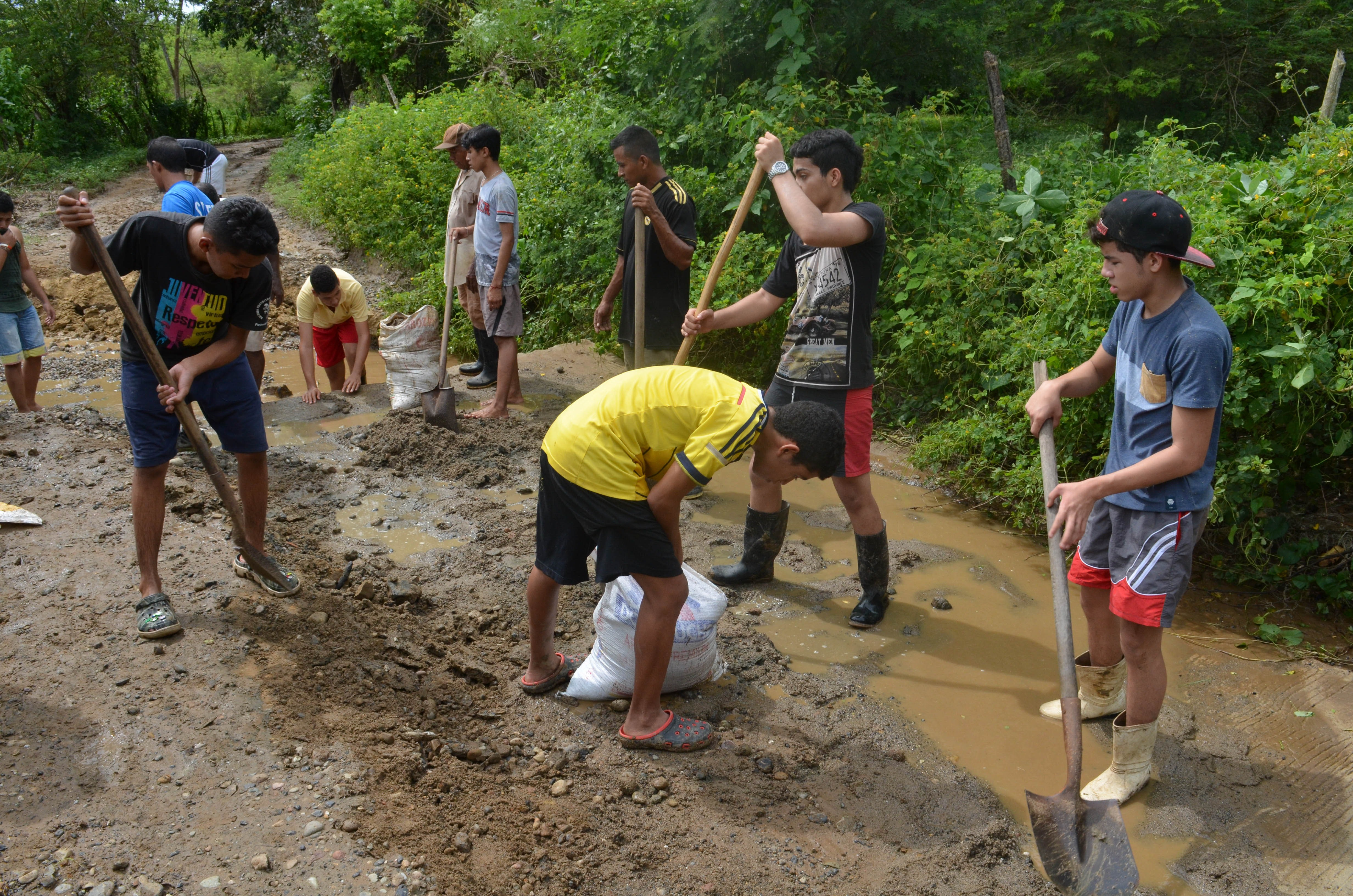 City teens work hard filling in the washed-out road. Credit: Ainsley Herrick