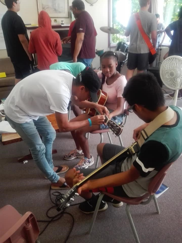 One of the youth from Cartagena teaches other campers some guitar basics.