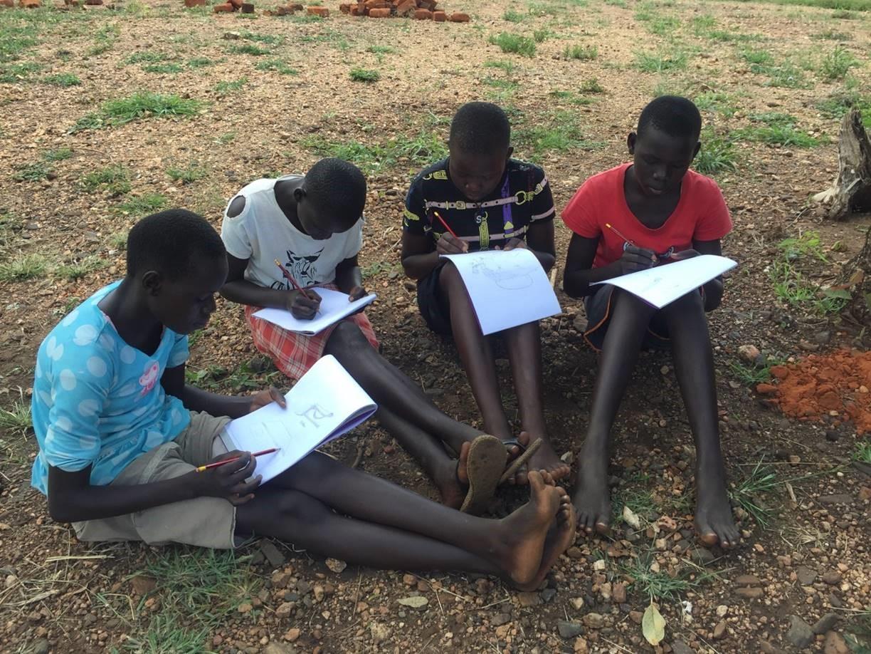 Children drawing at a Trauma Healing Workshop in Bidi Bidi Refugee Camp.