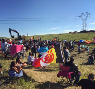Water protectors congregate next to a construction site for the Dakota Access Pipeline on a Monday morning as a crew arrives with machinery and materials to begin cutting a work road into the hillside. The flag in the foreground belongs to the American Indian Movement. (Photo by Daniella Zalcman)