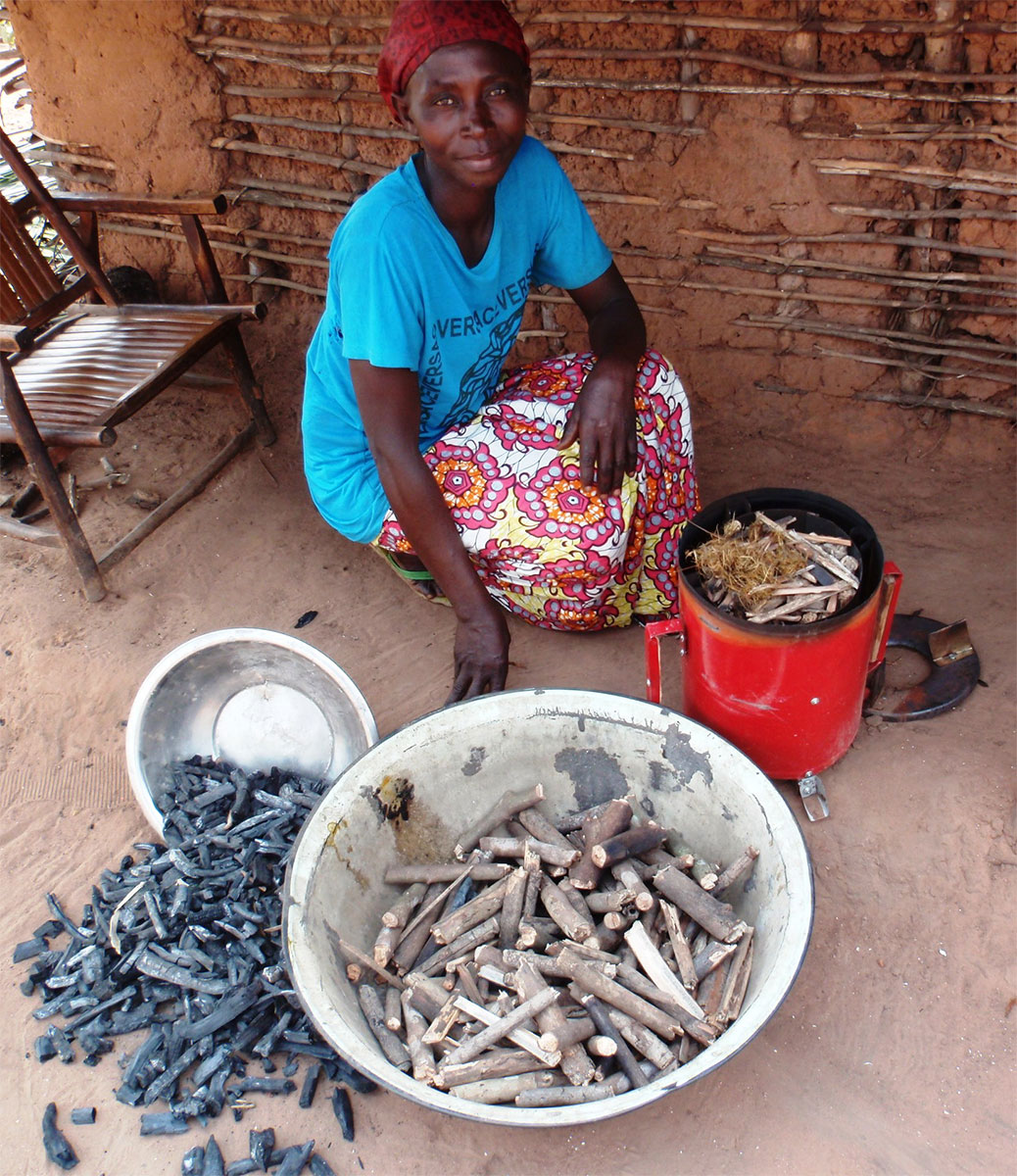 A woman at Mpoko village with the wood she uses to load her stove and the charcoal it has produced
