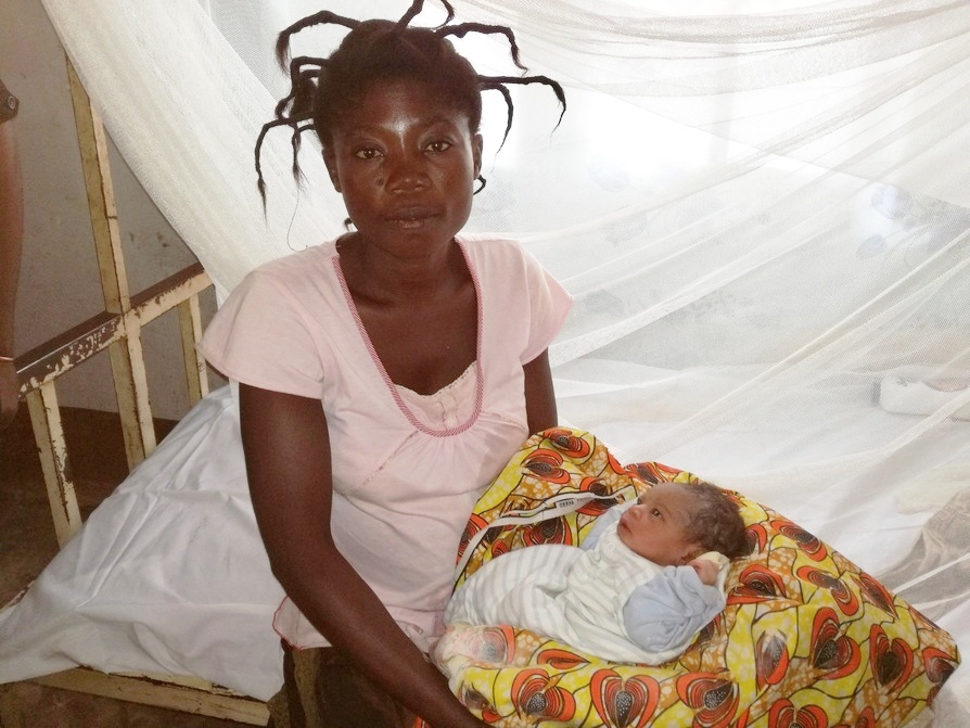 A mother with her newborn baby at Mapangu Reference Health Center, which is supported by the ASSP project. Mosquito nets provided by the ASSP project help protect mother and baby from mosquitoes that carry the malaria parasite.