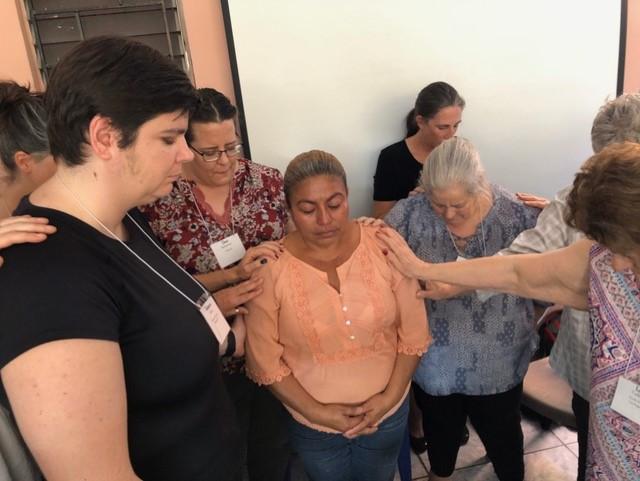 Praying with Juana, returned migrant in El Salvador.