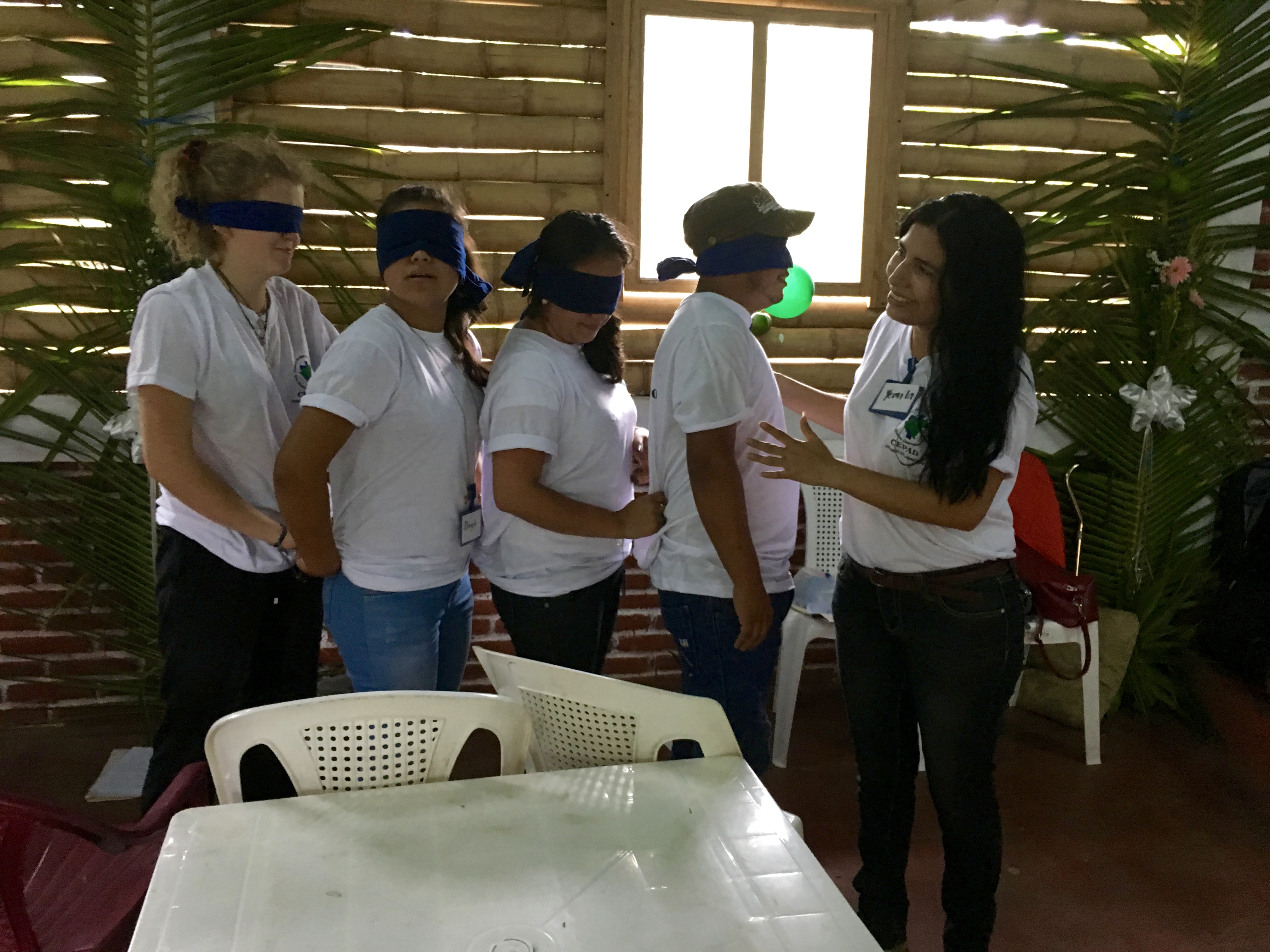 Yemila of CEPAD guides blindfolded participants through an obstacle course.