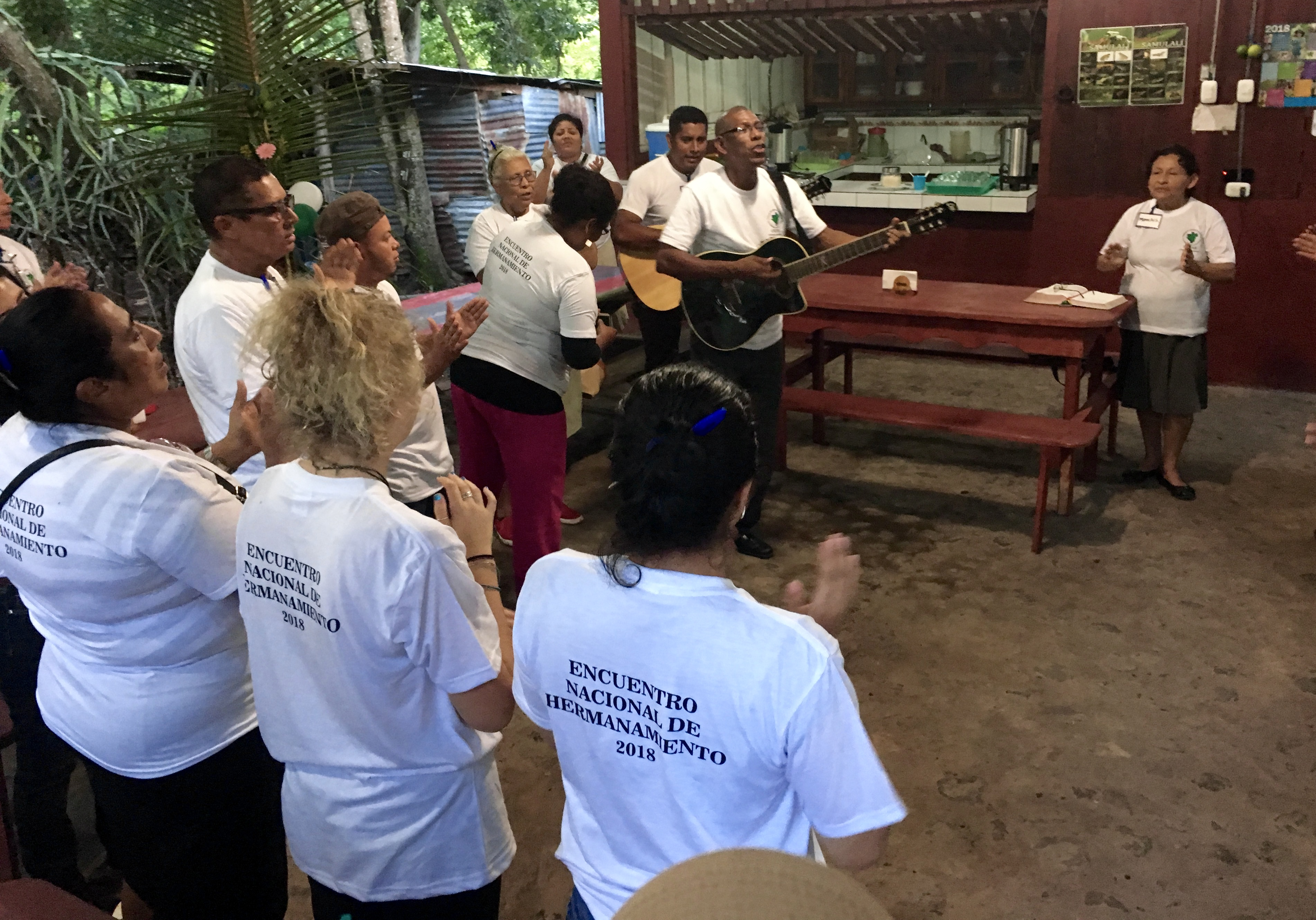 Pastor Moran Lampson from Bluefields leading the group in song before a meal together.