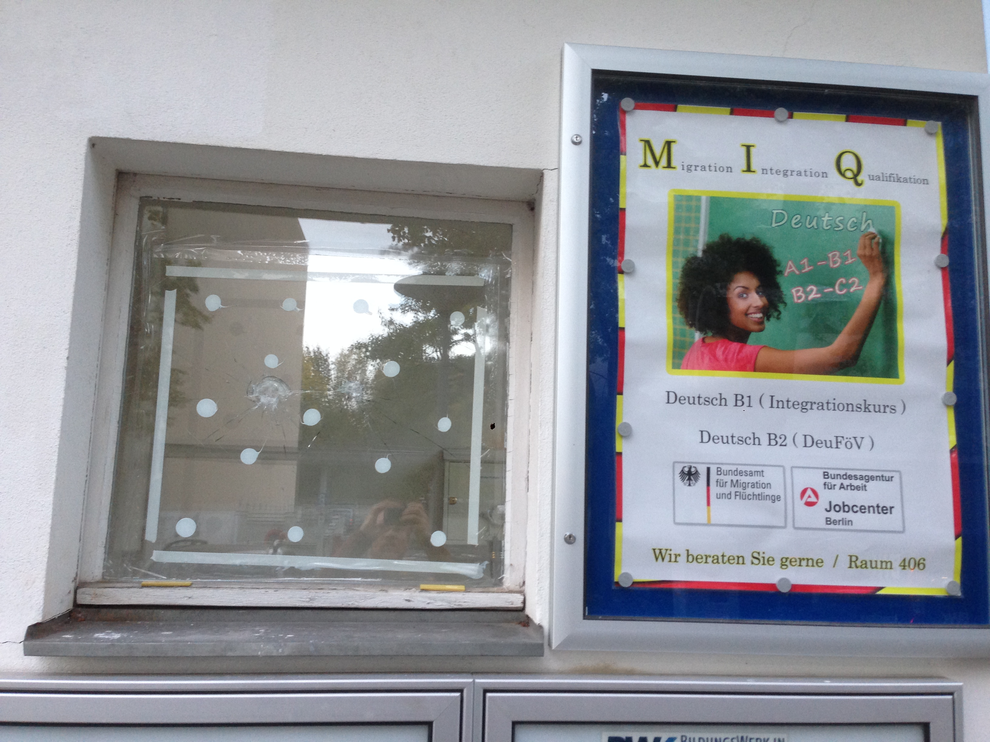 Window broken on purpose, next to an advertisement for integration classes for migrants.
