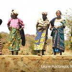 women standing on sand dam