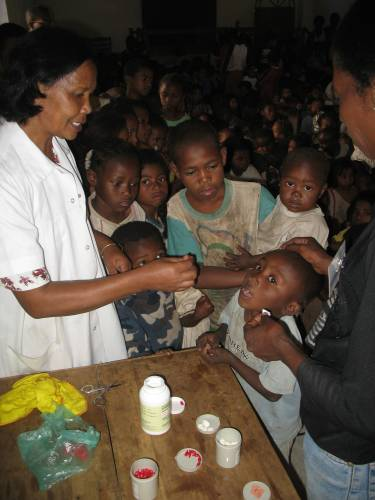 A nurse dispenses medication to children at the Antananarivo community centre where Pastor Helivao first met Mampianona.