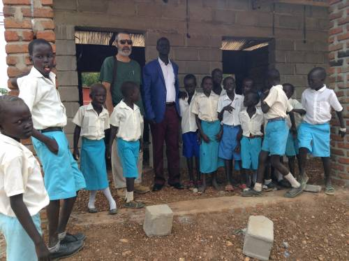 PC(USA) mission co-worker, Lynn Kandel, and the PCOSS education director, Rev. Stephen Nyang, with pupils proudly posing in front of the new classroom.